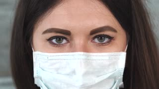 Close up shot of the brown eyes of a young woman who wore a protective mask on her mouth and nose, perhaps this is the face of an adult doctor