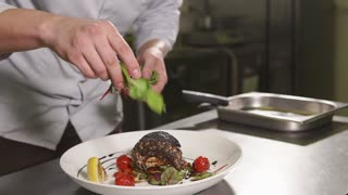 close up shot of the chef's hands, the man professionally throws leaves of spinach or salad on an appetizing piece of trout and fried vegetables, the dish will be served in a restaurant