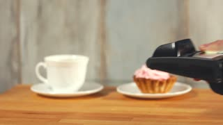 Close up shot of the contactless payment of dessert and coffee in a small cafe, a man's hands bring the smartphone to the terminal to make a purchase