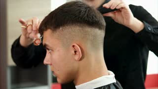 close up shot of the dark-haired head of a man who came to the hairdresser in order to change the haircut and change the image, the client expects a good service