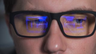 close up shot of the eyes of a young man wearing glasses who is watching a movie on a computer monitor. The video is reflected in the glasses of his glasses, the person looks closely