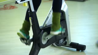 close up shot of the feet of a woman who pedals on an exercise bike. The athlete is engaged in cardio exercise on a bicycle in the fitness club for cardiovascular training