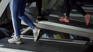 Close up shot of the feet of women walking along the treadmill during a sports training session. Athletes are dressed in cross-country running shoes, which fix the leg from injuries and bruises.