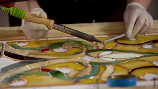 close up shot of the glazier's hands, a master in white gloves creates a glass stained glass window using an electric soldering iron, a woman decorating a pano.