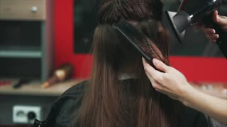close up shot of the hairdresser's hands, who dries dark and long hair with a hair dryer and comb, the beauty salon client is waiting for the completion of the image change