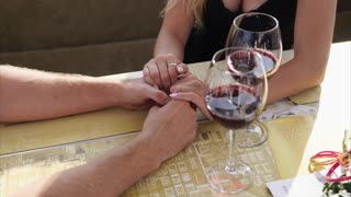 Close up shot of the hands of man and woman who drink wine in a restaurant or cafe during the day, on the table are glass glasses and a menu