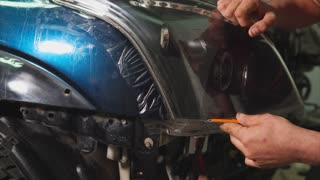 Close up shot of the hands of man who cut the vinyl film on the headlights of blue expensive car. This film protects the vehicle from the small chips and scratches.
