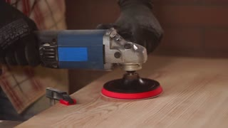 close up shot of the homemade table, which is polished with a nozzle on the drill, the man drives the tool over a piece of wood, the person is wearing gloves