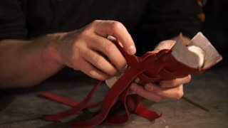 close up shot of the leather affairs of the master of the hand, who deals with the binding of the lines from the dermal material into a single braid, the man draws up the handmade product