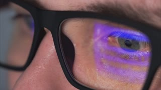 Close up shot of the male eye with long eyelashes with glasses who looks at the computer monitor. The lenses of the glasses reflect the picture of the film that the young man is looking at