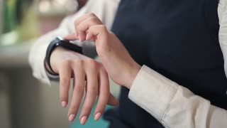 Close up shot of the manager's hands, who uses a smart watches to work. A woman can respond to incoming messages with smart watches that come on the smartphone.