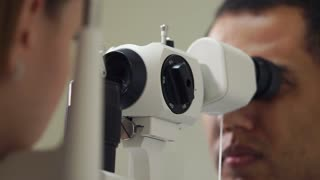 close up shot of the man's face, the person is working as an ophthalmologist in a private clinic and checks the eyesight for the patients, the doctor conducts biomicroscopy of the eyes