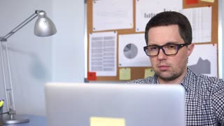 close up shot of the man's face, who works as a system administrator. A computer worker in glasses makes a program on a laptop for better functioning of the office system
