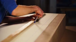 close up shot of the man's hands, people use a ruler and a felt-tip pen to hold an even line on the synthetic layer, the carpenter works in the workshop