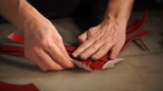 close up shot of the man's hands, who corrects the leather product, the master is engaged in manufacturing the handmade products in his workshop