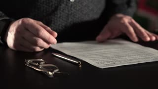 Close up shot of the man's hands, who signing documents, selective focus.
