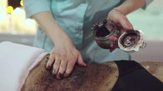 Close up shot of the masseur's hands applying coffee scrub to the woman's stomach in order to remove the dead cells and regenerate skin. The masseur with light movement will squash the granules.