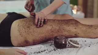 Close up shot of the masseur's hands, who puts a chocolate wrap on the girl's legs in order for the girl's skin to be softer and more elastic. Wrapping and scrubbing helps to relax in the spa center.