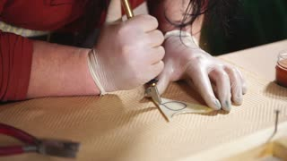 close up shot of the masters hands, the woman cuts the petal with the help of a sharp knife, the object she will use for the stained glass, glass maker works in the home workshop