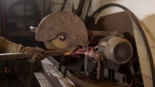 close up shot of the men's hands, who are engaged in the production of flat metal parts from iron, the man works with an industrial electric saw