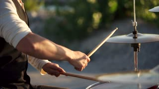 close up shot of the men's hands, who holds the drumsticks in their hand, the people energetically hit them on the plates in the daytime outside, maybe this is a street musician