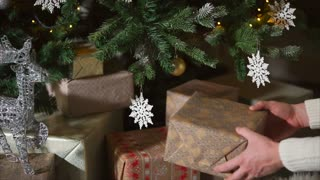 close up shot of the men's hands, who keeps the beautifully packed boxes with gifts, the person puts them under the tree, then the family opens the boxes during the celebration of the new year