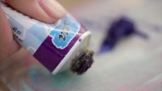 close up shot of the process of applying oil paint on the artist's palette in order to draw a still life or a portrait, a person applies a purple color on the board