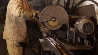 close up shot of the process of creating an even detail in an industrial plant, sparks flying in different directions, a worker in special clothes