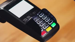 Close up shot of the process of paying a bank card account, the man's hands hold a plastic card over the terminal, then the fingers enter the pincode