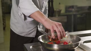 close up shot of the professional chef's hands, a man is cooking in the kitchen, he pours balsamic vinegar on vegetables that are stewed in a skillet