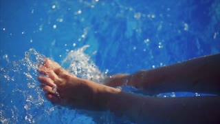 Close up shot of the slender legs of a young girl who babbles them in the cool water of the pool, splashes of water fly in different directions, they shine in the sun