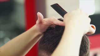 close up shot of the stylist hands, who cuts the dark hair of a young man, a visitor to a beauty salon changes her hair and immige in barbershop