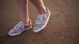 Close up shot of the woman's legs in shiny sneakers, who slowly stepped onto the wet sand, probably next to the sea or the river