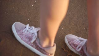 Close up shot of the woman's legs in shiny sneakers, who slowly stepped onto the wet sand, probably next to the sea or the river.