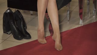 close up shot of the woman's thin legs, a lady dresses fashionable high-heeled shoes, she is in an expensive boutique for the purchase of clothes and clothes