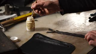close up shot of the worker's hands, the man is going to glue the zipper onto the leather part of the part in order to be able to open it, the man lubricates the zipper with a brush