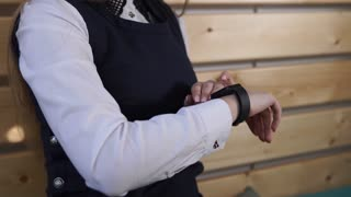 Close up shot of the young schoolgirl's hands, who enjoys the parents gifted - a smart watches. She will be able to show off to her classmates a new expensive gadget.
