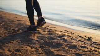 Close up shot of woman legs shod in black sneakers walking on the sand beach near the sea.