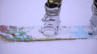 Close up shot of woman's legs with new bright snowboard equipment.