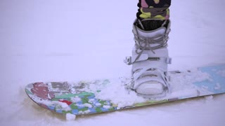 Close up shot of woman's legs with snowboarding equipment.