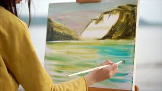 Close up view of abstract oil picture of landscape and female painter at work. Creative person