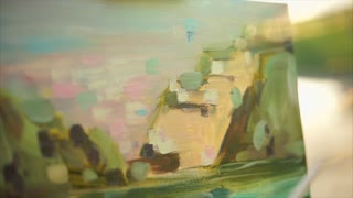 Close up view of process of painting oil picture. Female hand making smears with brush