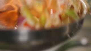 Close-up view through flame of flambe on a frying cherry tomatoes with paprika and onion. Chef is tossing up it for shifting with sauce