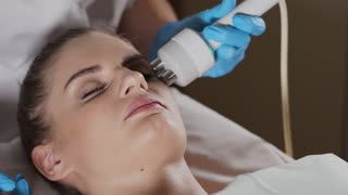 Close up woman with closed eyes getting rf-lifting in a beauty salon. Beautician uses hardware for Non-needle cosmetology