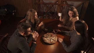Company of drunk women and man are discussing in a restaurant. Top view of people and table with pizza and cups with mixed drinks