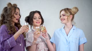 Concept of women's pajamas party. Three beautiful girlfriends drinking wine champagne and clinking with glasses.