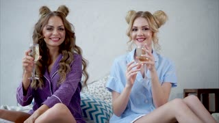 Concept of women's party. Two attractive women drinking champagne wine together. Clinking with glasses.