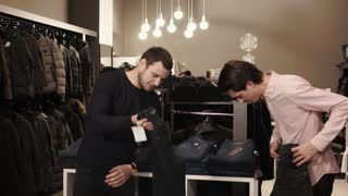 Consultant helps a handsome young man to choose a pair of jeans. He is attaching different pairs to his legs.