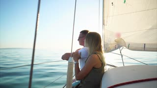 Couple in love is riding on the yacht in sunny summer day. Woman is embracing her man, speaking and enjoying of nature in no windy weather.