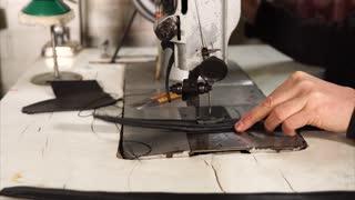 Craftsman making black leather handbag and stitching handles on sewing machine